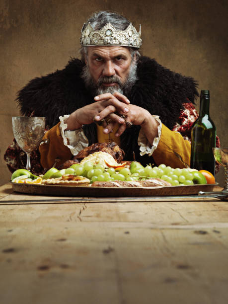 He feasts while the serfs starve A mature king feasting alone in a banquet hall royalty stock pictures, royalty-free photos & images