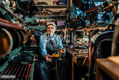 Photo of senior craftsman wearing hat and eyeglasses making luxury handmade man or woman shoes in his small workshop while looking at camera. Professional diligent old shoemaker heeling footwear on machine at the shop.