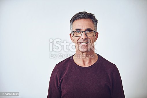 Studio portrait of a handsome mature man posing against a grey background