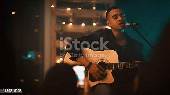 Shot of a young man singing and playing the guitar on stage