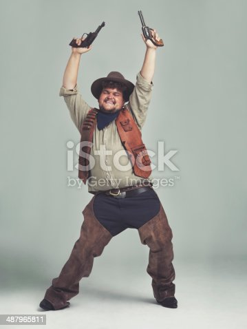 An overweight cowboy looking ecstatic with his pistols in the air