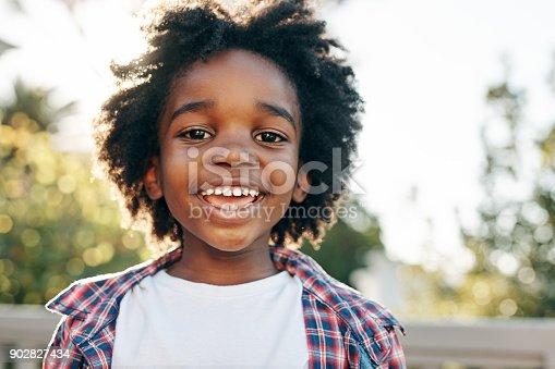 Portrait of a cheerful little boy smiling at the camera outside during the day