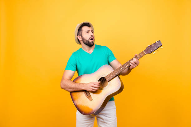 He is finding notes for the new popular song! Cheerful joyful excited musician playing the acoustic guitar, isolated on yellow background He is finding notes for the new popular song! Cheerful joyful excited musician playing the acoustic guitar, isolated on yellow background serenading stock pictures, royalty-free photos & images