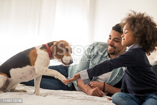 Portrait of an african american father and daughter enjoying spending time with dog in the bed.