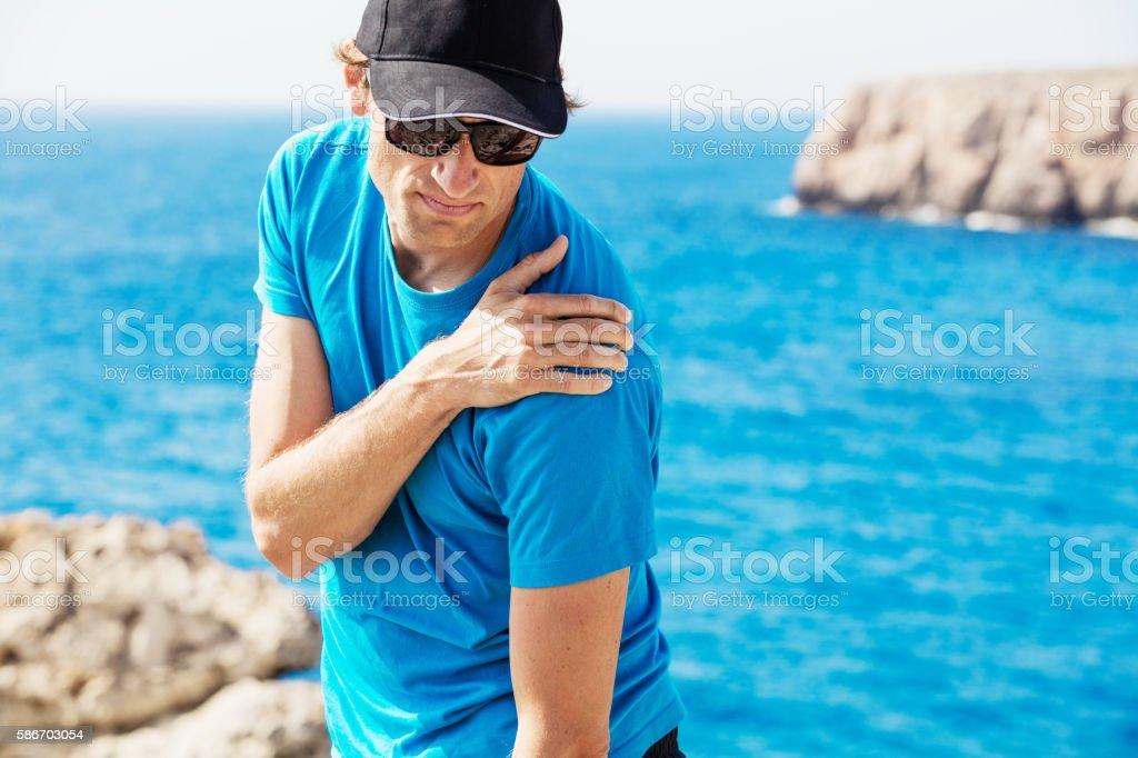 He is suffering under severe shoulder pain stock photo