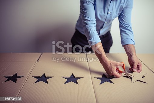 Businessman using scissors to cut five stars from a cardboard box. Customer satisfaction and best rating concept.