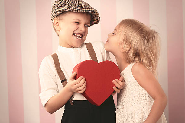 he isn't keen on kissing - little girls little boys kissing love stock photos and pictures