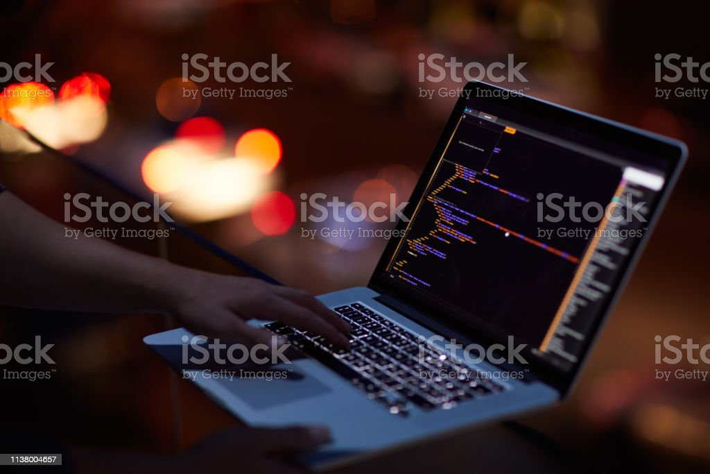 He knows his way around any network Shot of an unrecognisable hacker using a laptop in the dark Adult Stock Photo