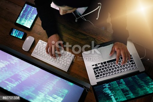 High angle shot of a hacker cracking a computer code in the dark
