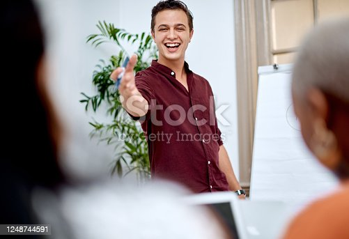 Shot of a young businessman using a whiteboard while giving a presentation to his colleagues in an office