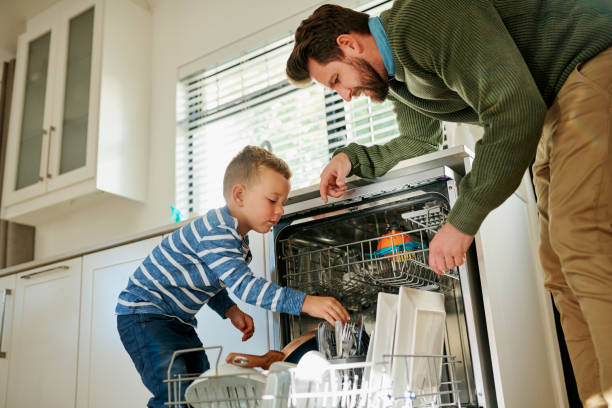 He knows how to pack the dishes in the machine Shot of a father and his little son using a dishwashing machine together at home dishwasher stock pictures, royalty-free photos & images