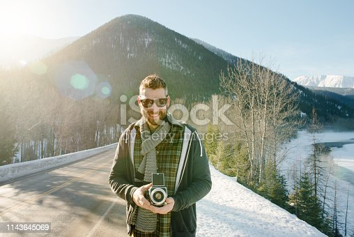 Shot of a handsome young man holding a retro camera outdoors on a winter day