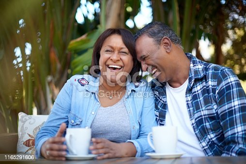 Cropped shot of an affectionate mature couple enjoying a cup of coffee together while sitting outside surrounded by nature