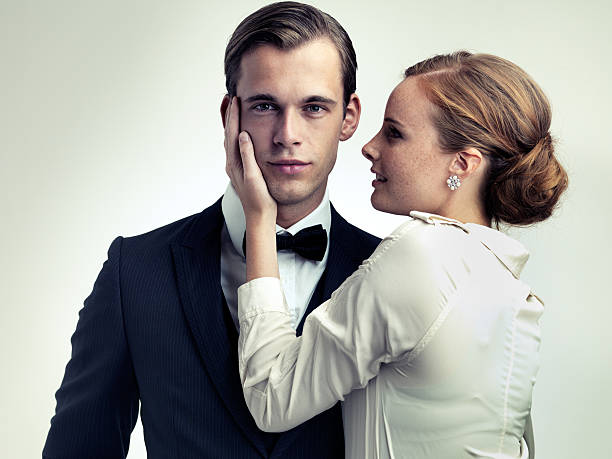 He makes them weak at the knees A cropped studio portrait of a dapper young man with a beautiful girl on his arm evening wear stock pictures, royalty-free photos & images