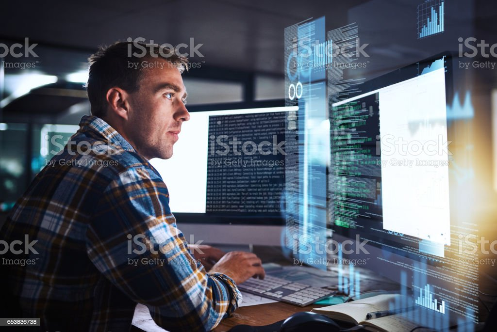 He puts the pro in programmer Shot of a young programmer working at his computer with an overlay of computer graphics Adult Stock Photo