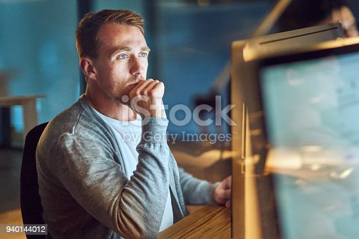 Shot of a young man using a computer during a late night in a modern office