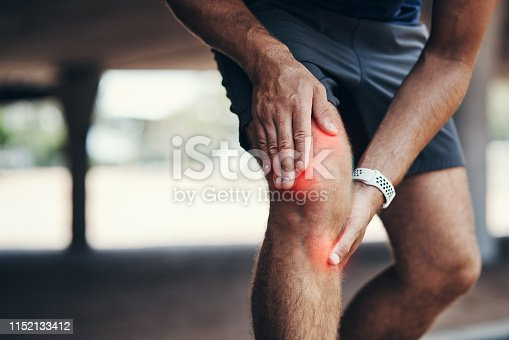 Closeup shot of an unrecognizable man holding his knee in pain while exercising outdoors