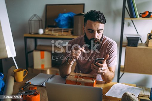 Photo of young man using app for smart phone tracking delivery package in his office