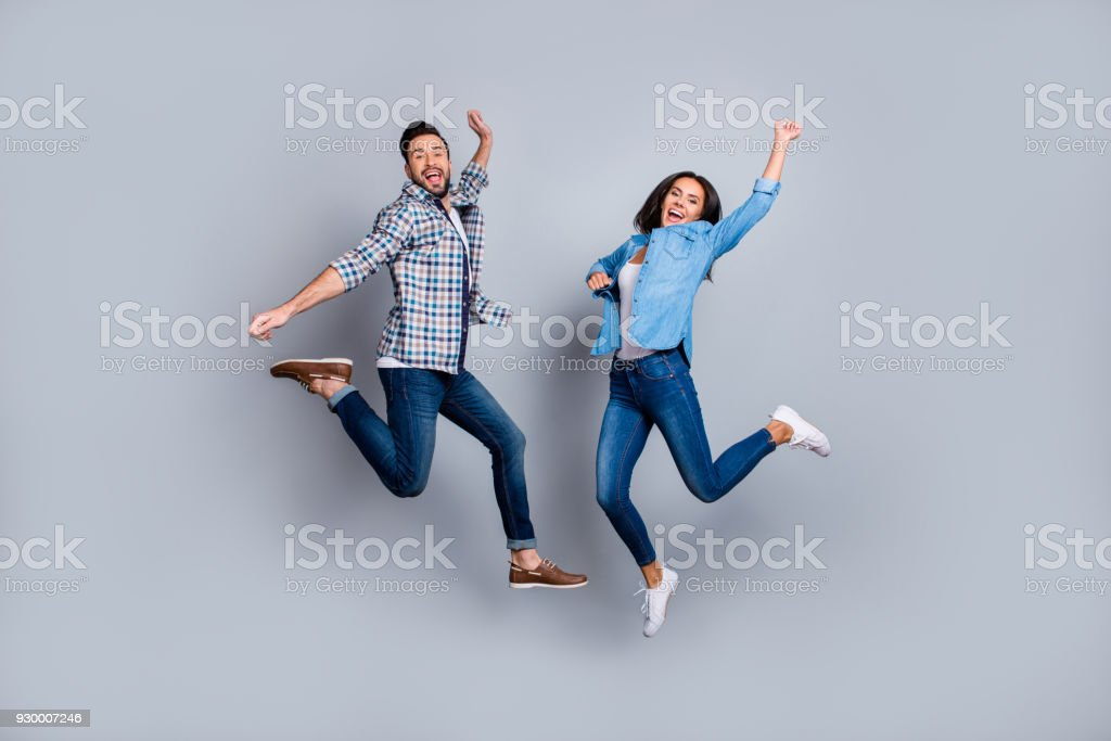 He vs She full length portrait of attractive, playful, cheerful, comic couple in casual outfit, jeans, shirts jumping  over grey background stock photo