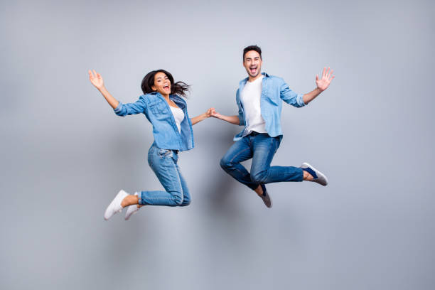 he vs she full length portrait of attractive, playful, cheerful, hispanic couple in casual outfit jumping with opened mouths over grey background - jeans stock photos and pictures