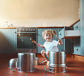Portrait of an adorable little boy playing with pots in the kitchen