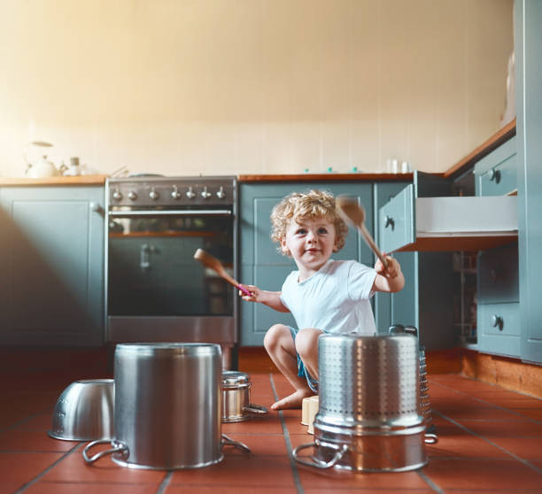 He wants to be a drummer when he grows up Portrait of an adorable little boy playing with pots in the kitchen drummer stock pictures, royalty-free photos & images