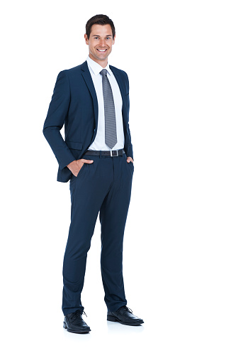Full length portrait of a handsome businessman standing with his hands in his pockets isolated on white