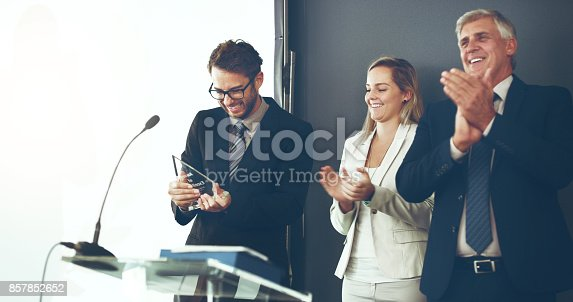 Cropped shot of two corporate businesspeople applauding the recipient of an award during a ceremony