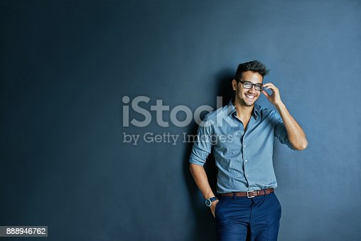 Studio shot of cheerful young man with glasses standing with one hand in his pocket while looking at the camera