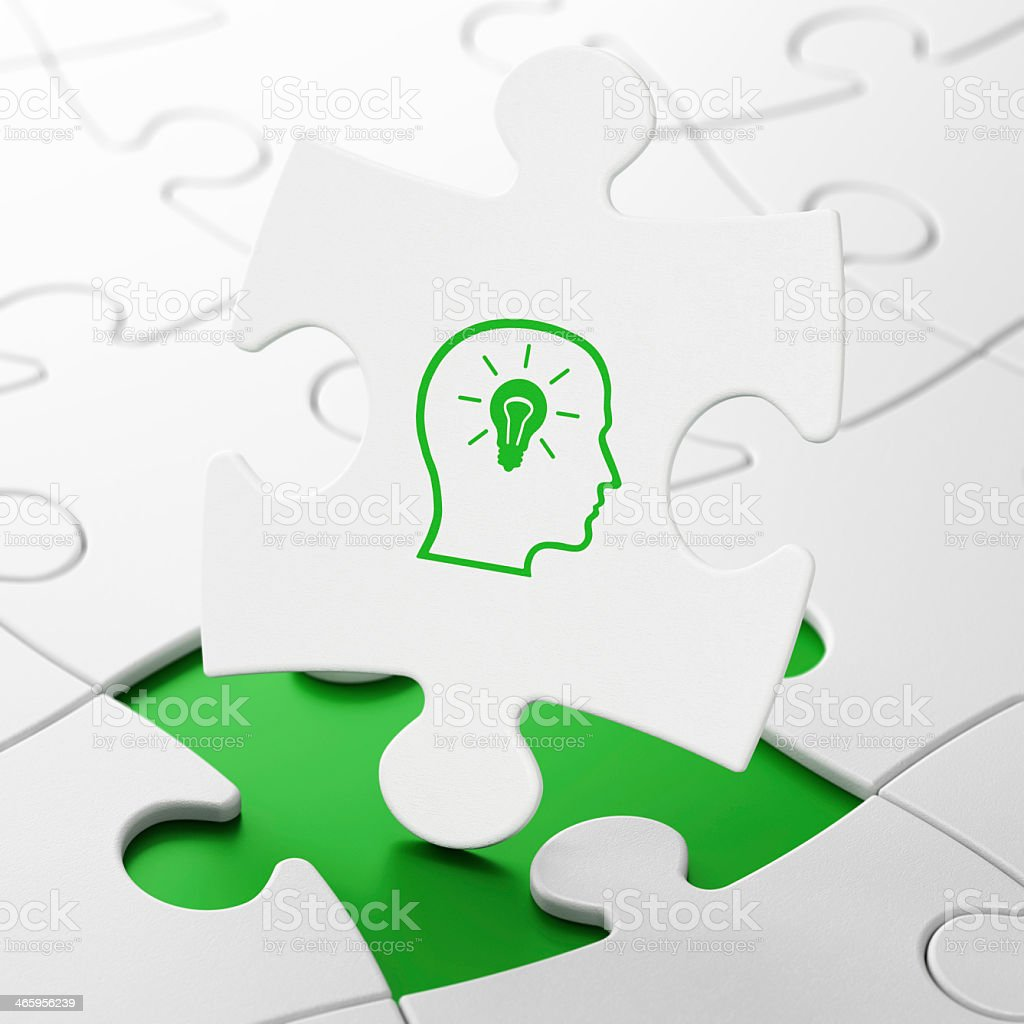 Head and lightbulb on puzzle background as education concept stock photo