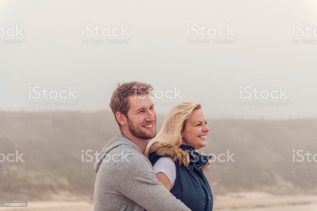 Head and shoulder portrait of a happy couple at Fistral beach, Newquay, Cornwall on an Autumn day. stock photo