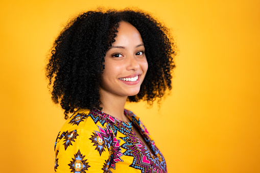 Three-quarter profile of mid 20s black woman with curly medium-length hair wearing dashiki-style top and smiling at camera against dark yellow background.
