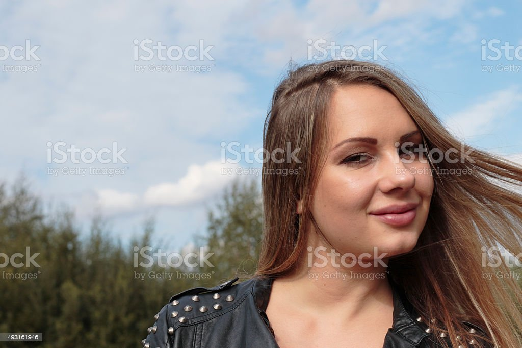 Wind-blown blonde haired woman against sky outdoor Polish girl stock photo