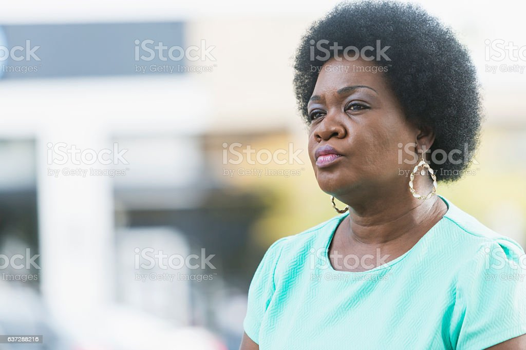 Head and shoulders of serious mature black woman stock photo
