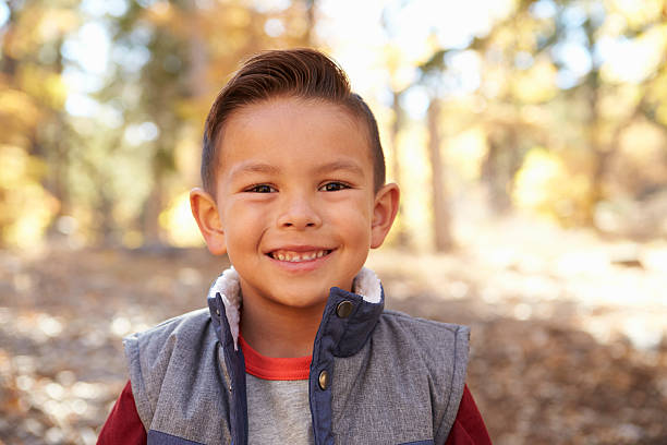 Head and shoulders portrait of a Hispanic boy in a forest stock photo