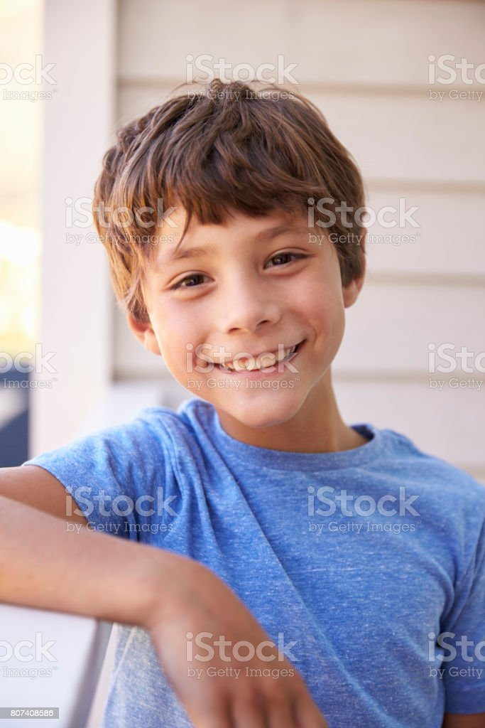 Head And Shoulders Portrait Of Boy Outside House stock photo