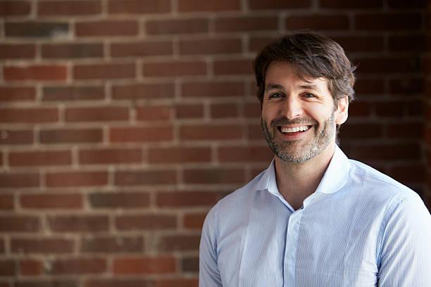 head and shoulders portrait of businessman in office - mid volwassen mannen stockfoto's en -beelden