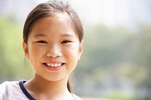Head And Shoulders Portrait Of Chinese Girl Head And Shoulders Portrait Of Chinese Girl In Park Smiling At Camera 8 9 years stock pictures, royalty-free photos & images