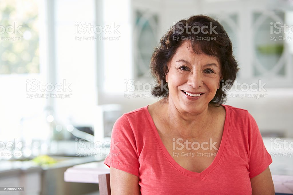Head And Shoulders Portrait Of Senior Hispanic Woman At Home stock photo