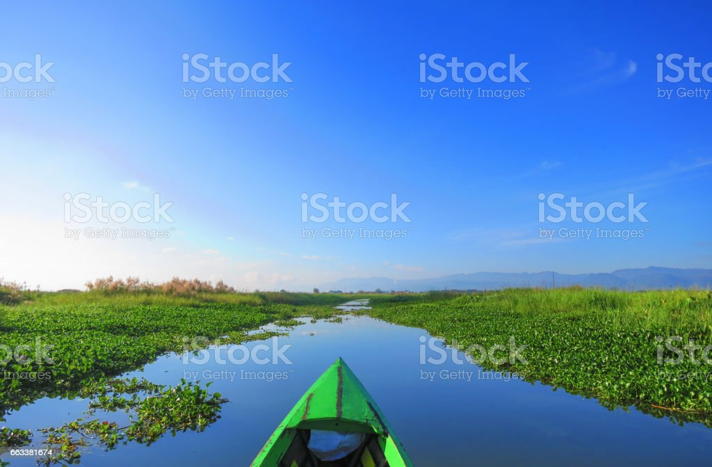 Head Cam POV view on a small green boat going through Lake Inle, Myanmar on a hot sunny day with crystal blue skies - surrounded by water farm vegetations ground on the lake. stock photo