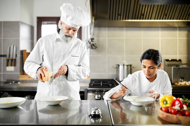 Head chef and sous chef working together in the kitchen stock photo