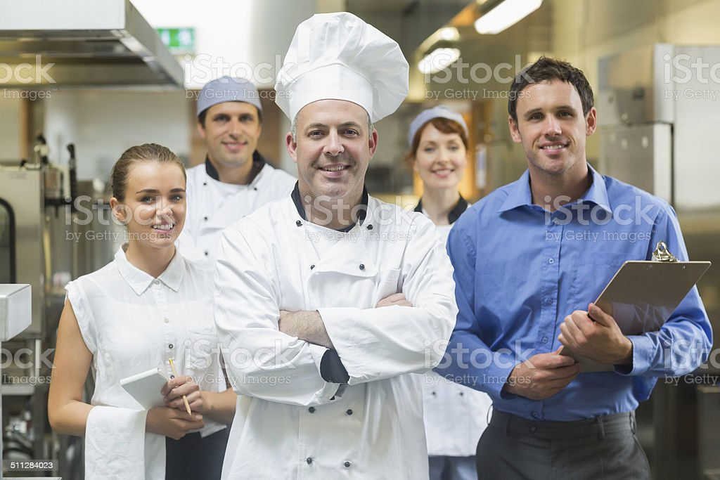 Head chef posing with the team behind him stock photo