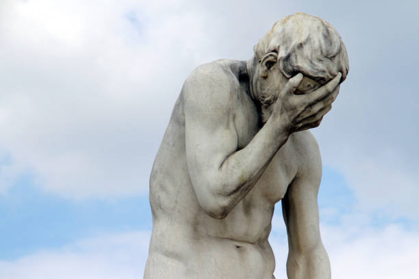 Head in hands: Facepalm statue, ashamed, sad, depressed Marble statue with head in hands in front of blue sky (Statue: