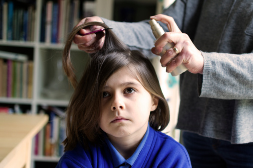 A mother spraying her daughter's hair with head lice treatment