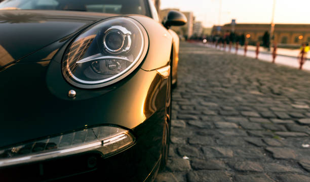 Head light of a porsche car Izmir - Turkey - March 5, 2017: Head light of a black Porsche car on sunset. porsche stock pictures, royalty-free photos & images