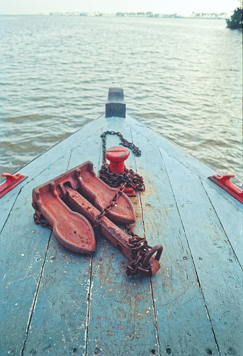Head of a colourful fishing boat with iron rustic anchor on Sea backwater at Alleppey Kerala India\