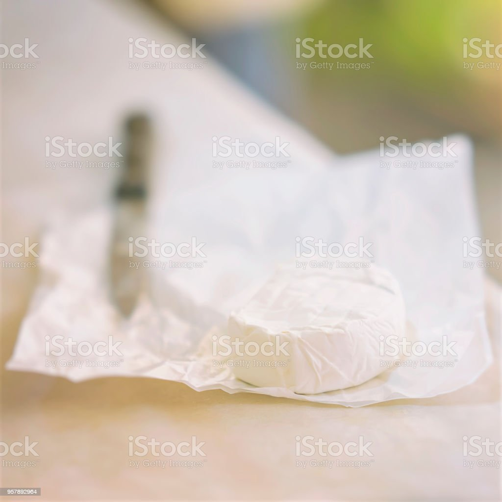 Head of brie cheese in white paper packaging, knife. Gastronomic dainty products on market counter, real scene in the food market. Selectiv focus, light background stock photo