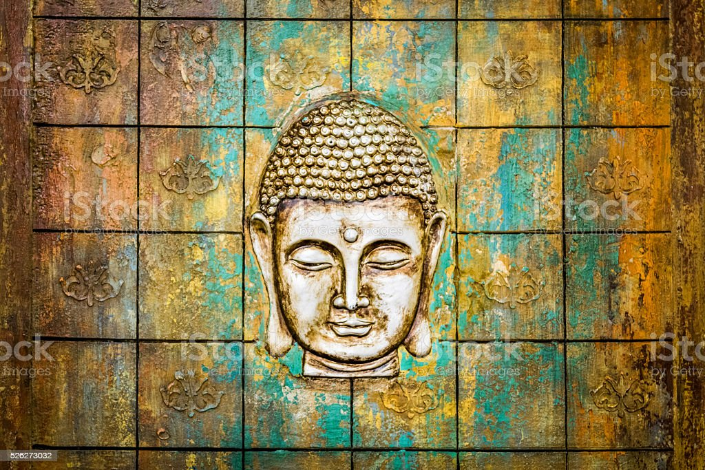 Head of Buddha carved in a wooden door. stock photo