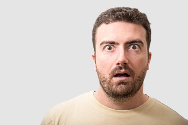 Head of surprised man portrait on gray background - foto stock
