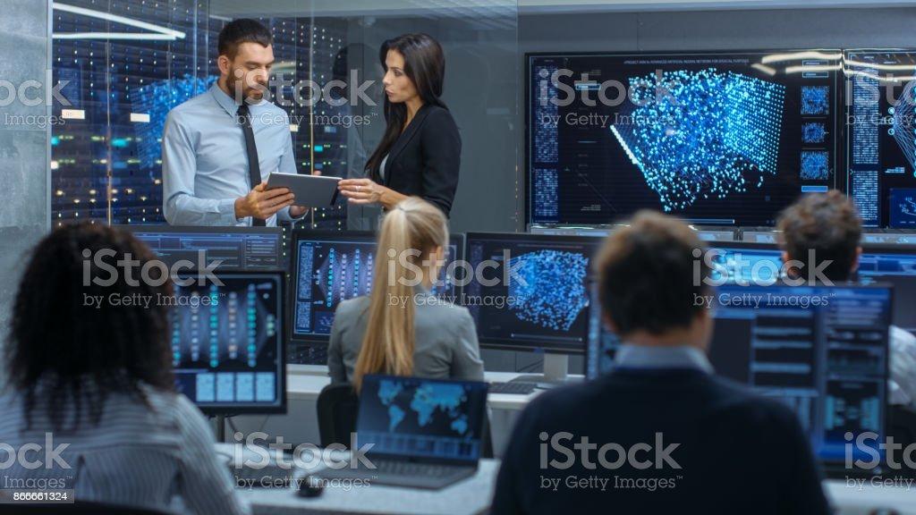 部門やプロジェクト マネージャーの頭は、タブレット コンピューターのデータを使用して作業プロセスをについて説明します。多民族のチームは、統合された機械学習とニューラル ネットワークを構築します。 ストックフォト